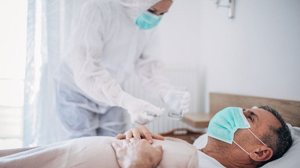 man in mask in hospital bed with medic in full PPE