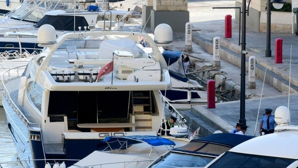 """Policemen leave the luxury yacht Gio, owned by Yorgen Fenech, a businessman, after it was escorted back into the Portomaso Marina in St Julian""""s, Malta"""