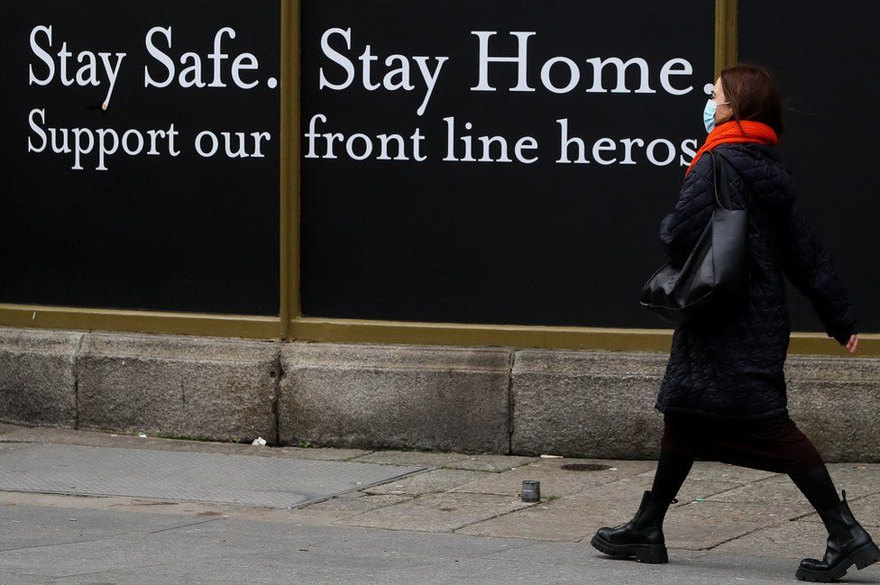 """A woman walks past a shop hoarding which reads: """"Stay safe. Stay home. Support our frontline heroes."""""""