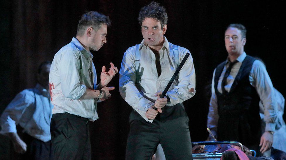 A scene from The Exterminating Angel, performed at New York's Metropolitan Opera, featuring three unkempt men with bloodstains