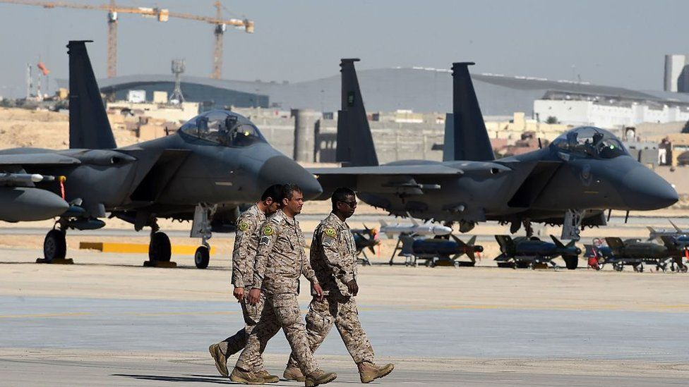 Saudi army officers walk past F-15 fighter jets, GBU bombs and missiles displayed during a ceremony marking the 50th anniversary of the creation of the King Faisal Air Academy at King Salman airbase in Riyadh on January 25, 2017