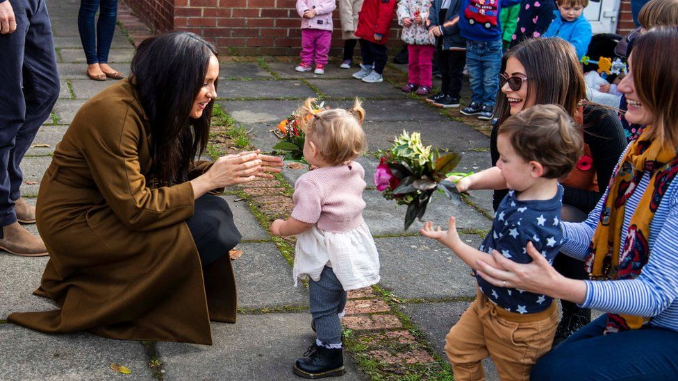 The Duchess of Sussex crouches down to greet a toddler outside Windsor's Broom Farm Community Centre