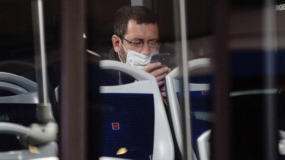A worker wearing a protective mask looks at his phone on a bus in Valladolid, northern Spain (13 April 2020)