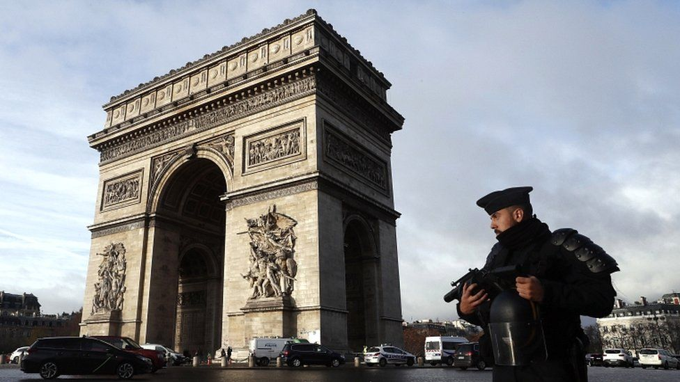 A French riot police officer stands guard in front of the Arc de Triomphe after violent protests in Paris, France, on 2 December 2018