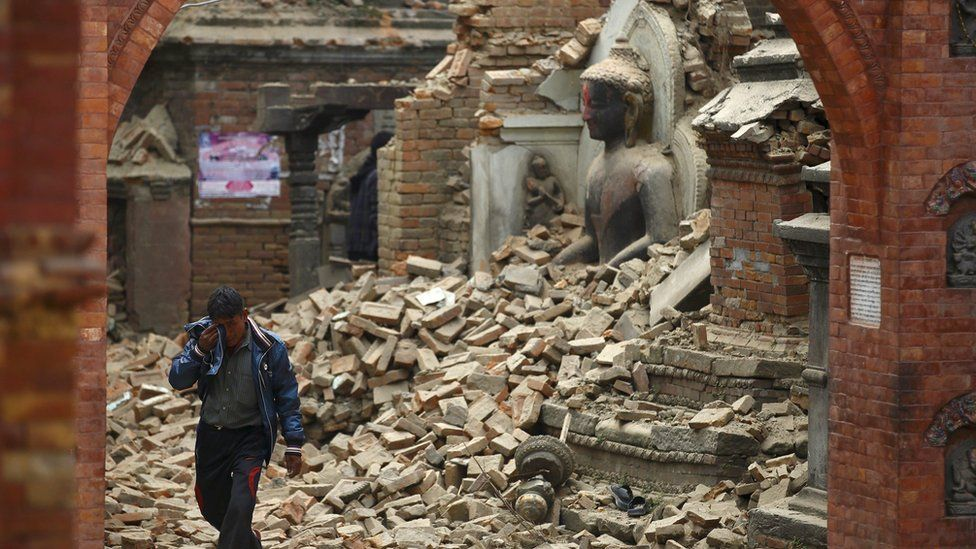 A man cries as he walks on the street while passing through a damaged statue of Lord Buddha a day after an earthquake in Bhaktapur, Nepal April 26, 2015