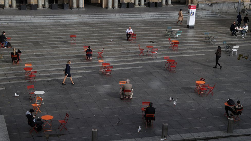 A few people sit at distanced tables in Martin Place in central Sydney