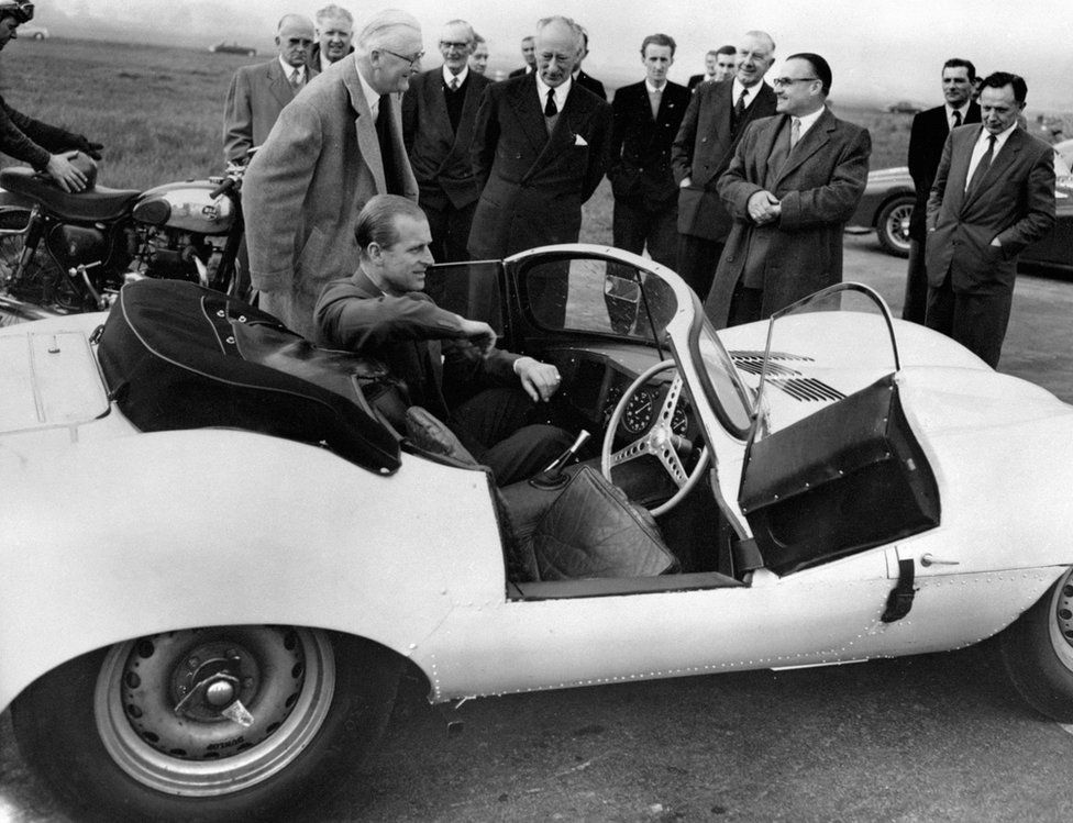 The Duke of Edinburgh is seen trying the passenger's seat of the new 3.5 litre Jaguar XKSS sports car during his visit to the Motor Industry Research Association's headquarters near Nuneaton, Warwickshire