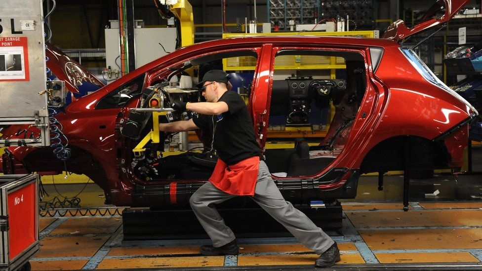 A dashboard being fitted on a car manufacturing line