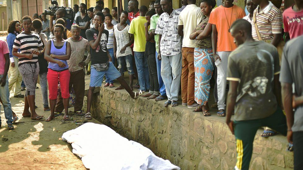 People gather around the body of a man shot dead in the Nyakabiga neighbourhood of Bujumbura on 21 July 2015