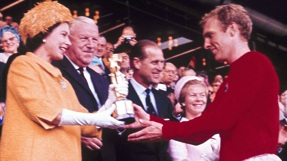 "Queen Elizabeth II presents the World Cup, the Jules Rimet trophy, to England""s team captain Bobby Moore on 30 July, 1966"