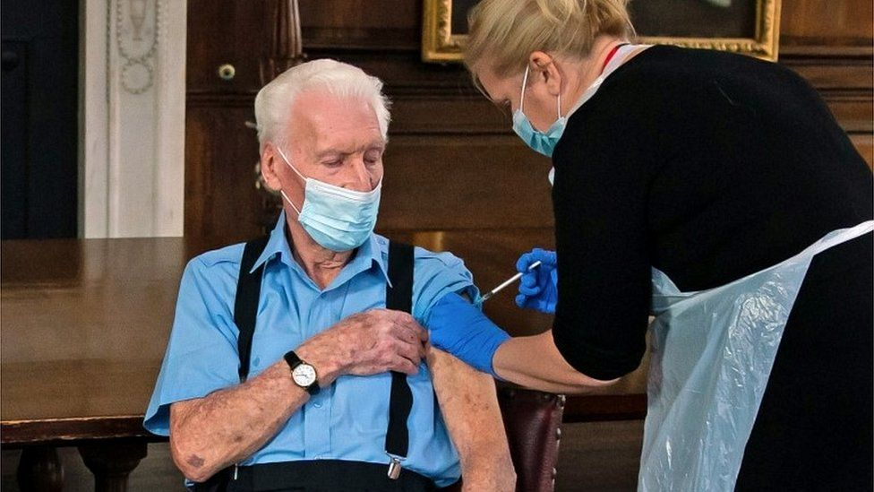 Chelsea Pensioner Bob (Robert) James Sullivan is injected with the Pfizer/BioNTech Covid-19 vaccine by Pippa Nightingale