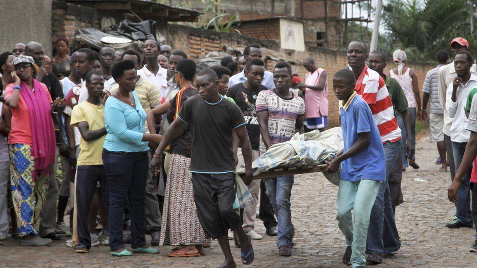 Men carry away a dead body in the Nyakabiga neighborhood of Bujumbura, Burundi