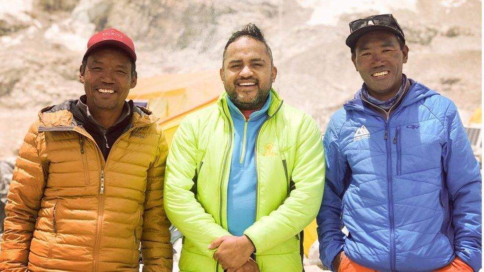 Brothers Lakpa (L) and Kami Rita (R) pose for a photo with a host a visiting filmmaker (C)