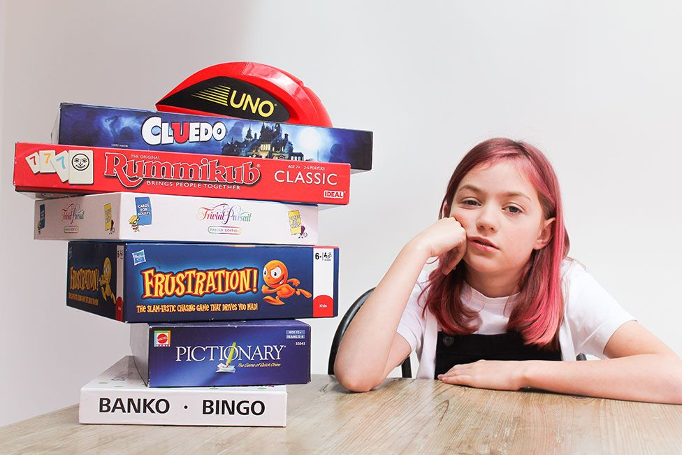 A girl looks bored next to a stacked pile of board games