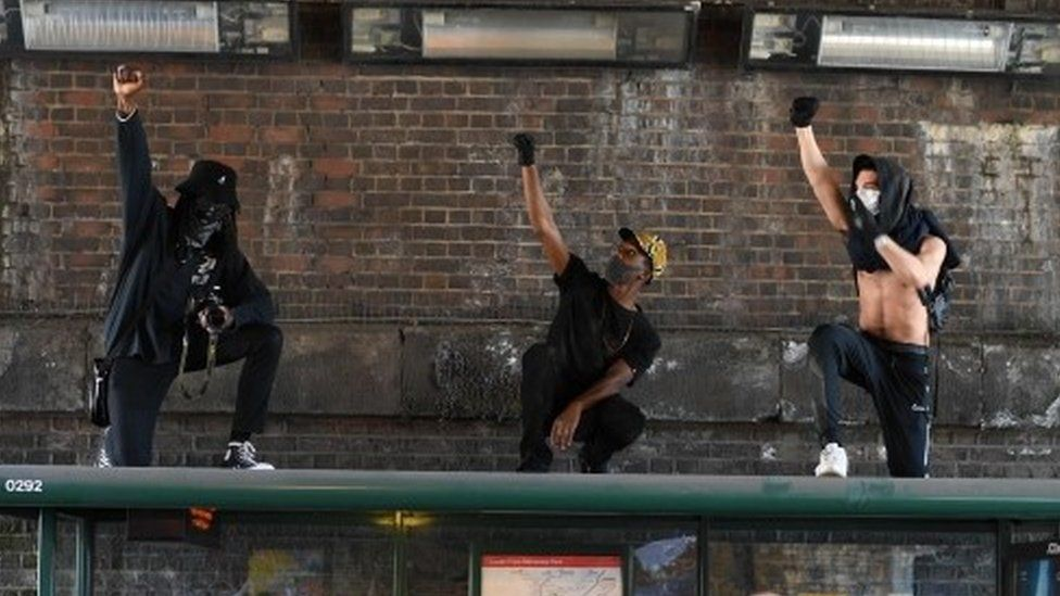 Three men demonstrate on top of a bus stop