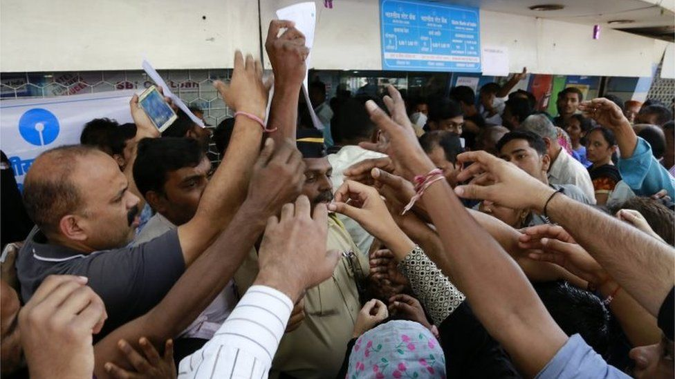 Indians stretch out their hands to collect withdrawal slips from a police officer to deposit and exchange discontinued currency notes outside the State bank of India in Mumbai, India, Thursday, Nov. 10, 2016.