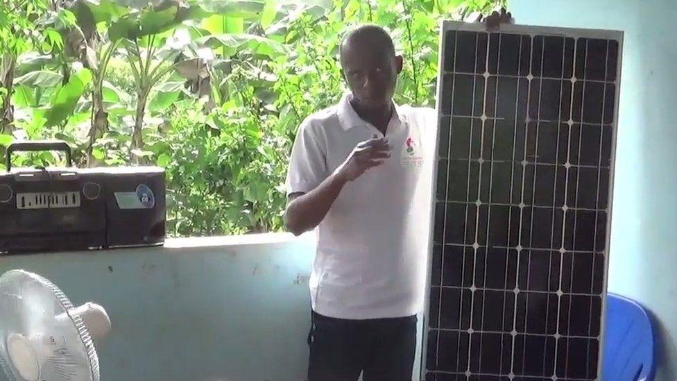 Man explaining how solar panels work to villagers