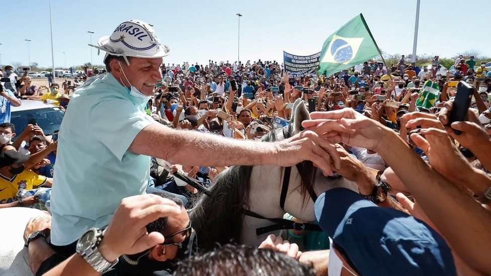 A handout photo made available by the Brazilian presidency in which Brazilian President Jair Bolsonaro is received by hundreds of people on a visit to the city of Sao Raimundo Nonato