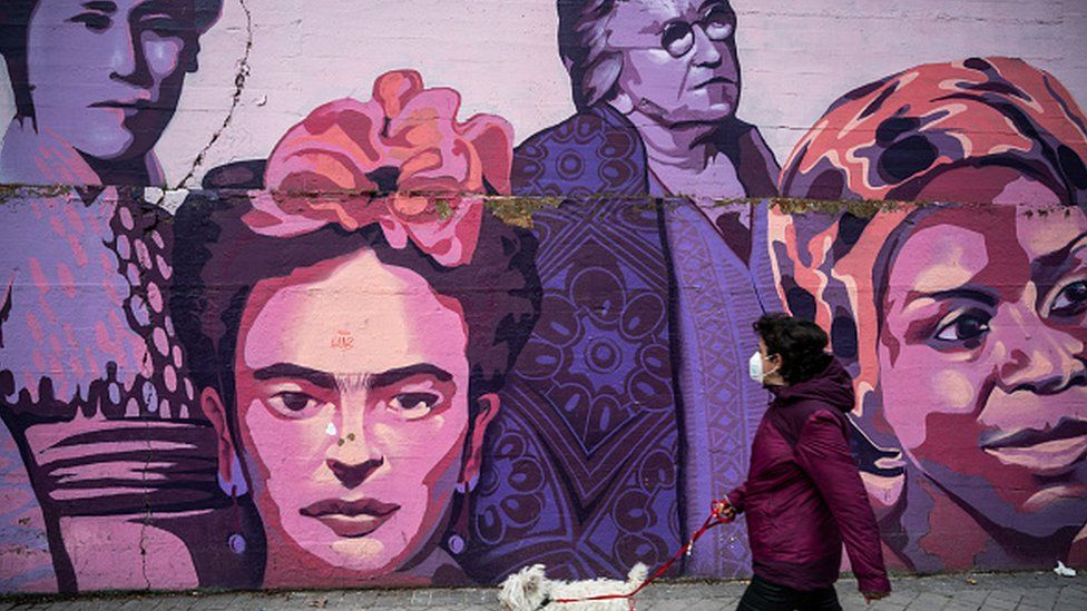 A woman with a dog walks past a feminist mural in Madrid