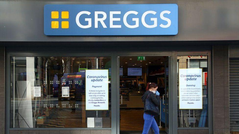 Woman wearing mask walks past Greggs shop