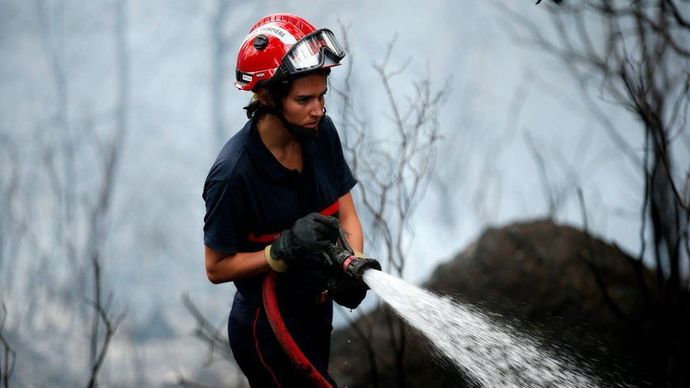 A firefighter tackles a forest fire in Carros near Nice, southern France