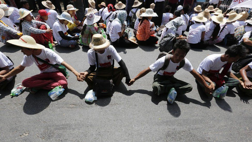 Protesters sitting on a road join hands as they demand labour rights