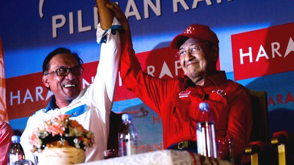 Malaysian Prime Minister Tun Mahathir Mohamad (R) raises up Anwar Ibrahim's hand