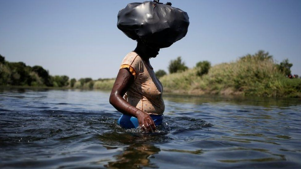 A migrant woman asylum seeker walks through the Rio Grande river to cross the border between Ciudad Acuna, Mexico and Del Rio, Texas