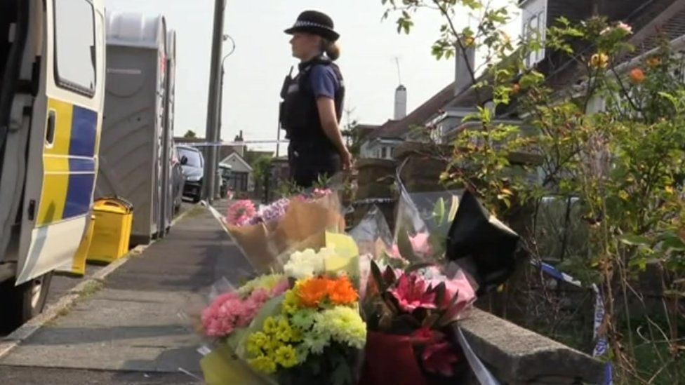 Police and flowers outside Shana Grice's home