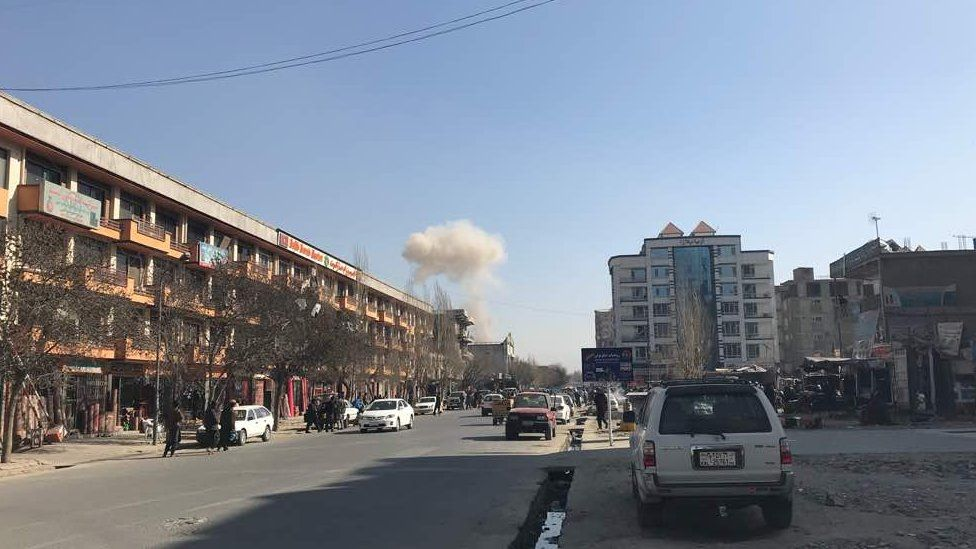 Kabul street with smoke in distance