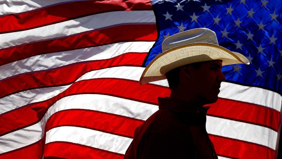 Man in a cowboy hat silhouetted against the US flag