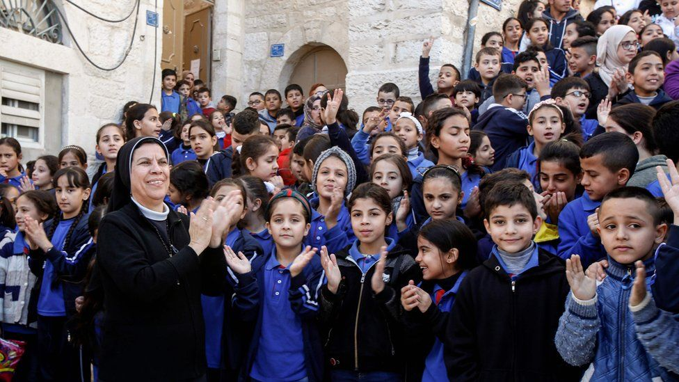 A nun claps along with Palestinian school children as they await the return of the relic in Bethlehem, 30 November, 2019