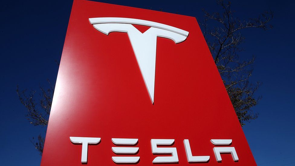 Tesla logo in a sign posted in a Tesla showroom
