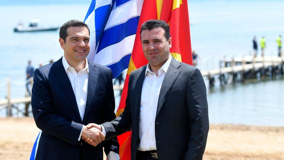 Macedonian Prime Minister Zoran Zaev (R) welcomes Greek Prime Minister Alexis Tsipras on the shore of Lake Prespa on June 17, 2018