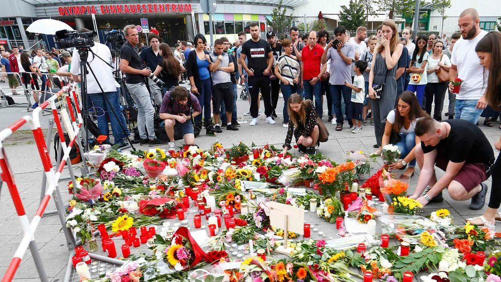 People look at the growing collection of flowers and candles for victims of the Munich shooting (23/07/2016)