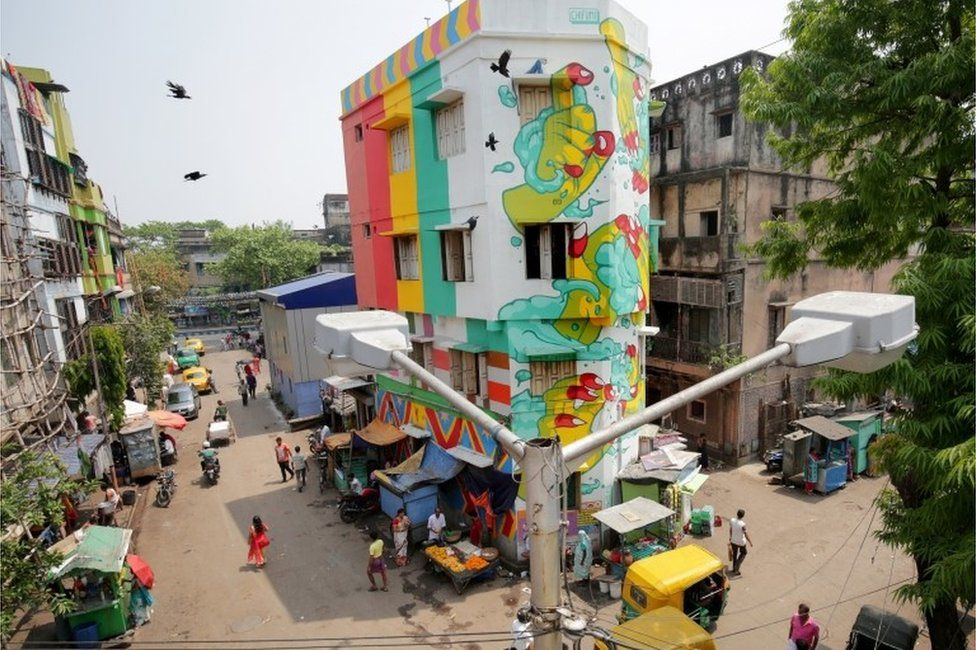 Indian commuters walk past a painted building at Sonagachi red light district in Kolkata,
