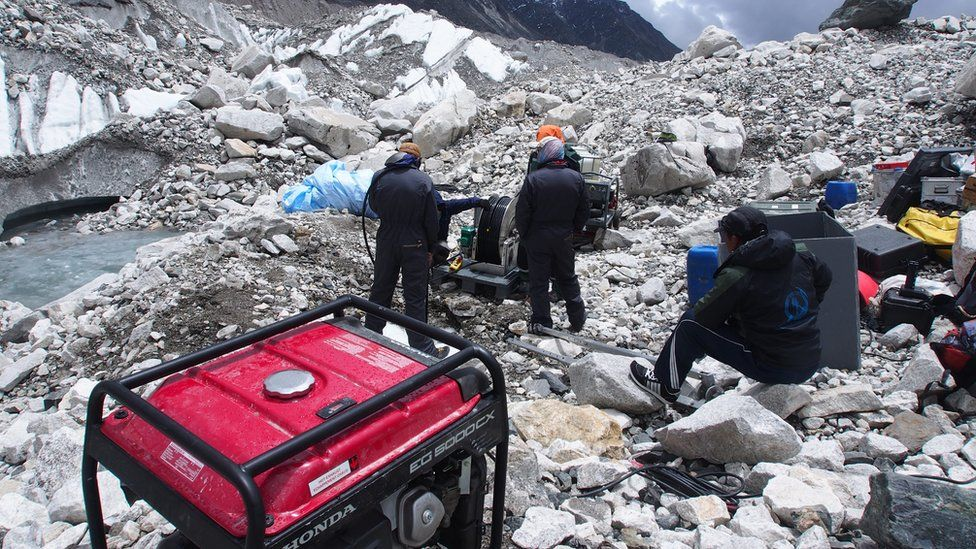 The team drill into the glacier