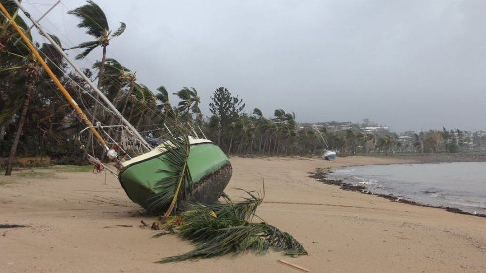 A yacht is stranded on the sand at Airlie Beach, in Queensland's Whitsunday region