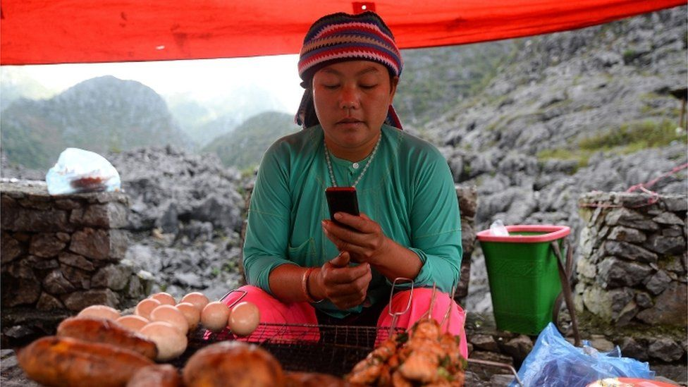 An ethnic Hmong woman checks her phone at her market stall (Oct 2018)