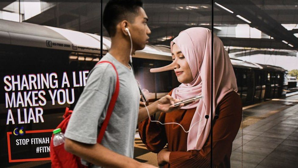 A commuter walks past an advertisement reading 'sharing a lie makes u a liar' at a train station in downtown Kuala Lumpur on March 26, 2018.