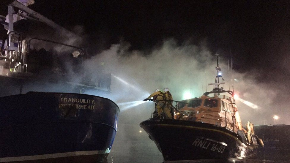 Lifeboat crew helping cool deck burning boat