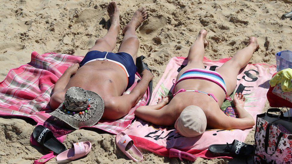 People sunbathe as they enjoy the warm weather on Boscombe beach in Dorset