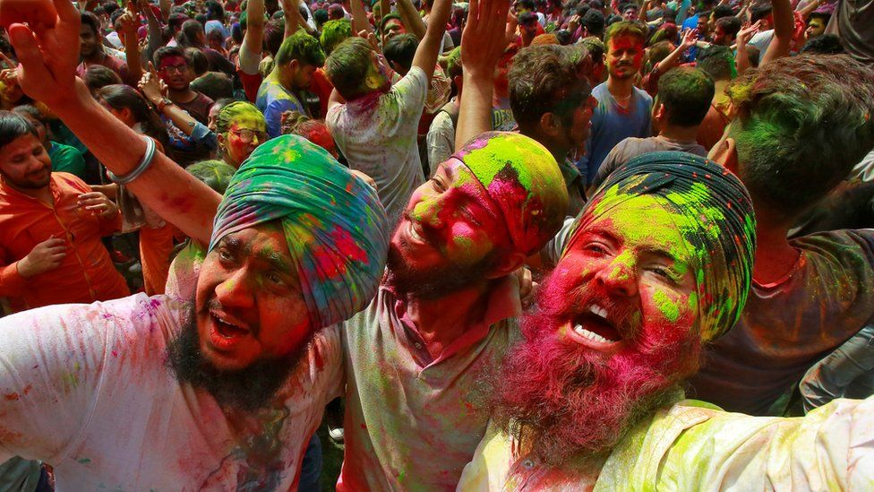 Students with their faces smeared in colourful powder dance