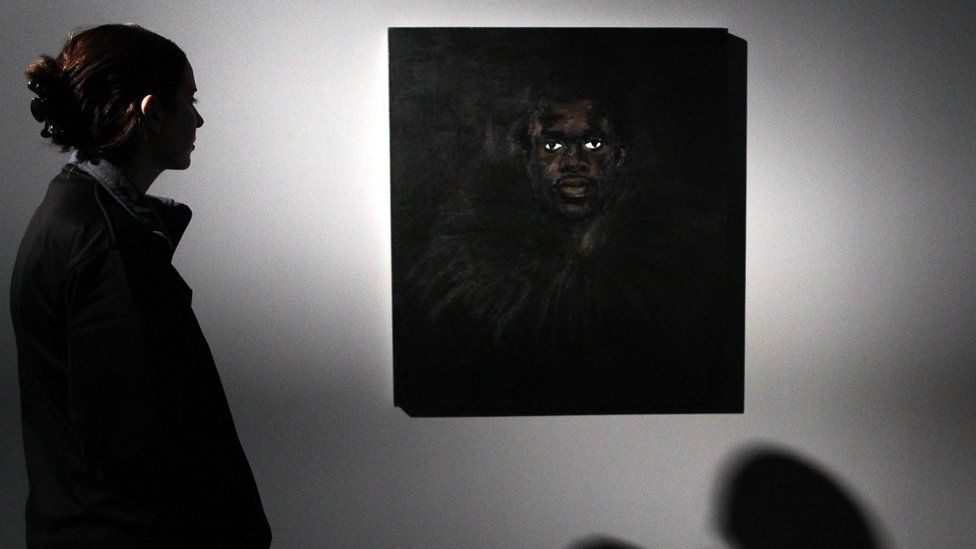 A visitor looks at a painting by Lynette Yiadom-Boakye