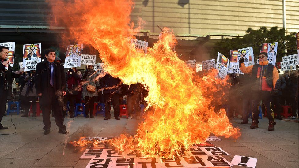 Protesters in South Korea standing around a large fire, demonstrating against North Korea's nuclear test