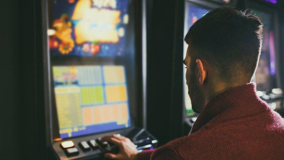 Man gambling on fruit machine