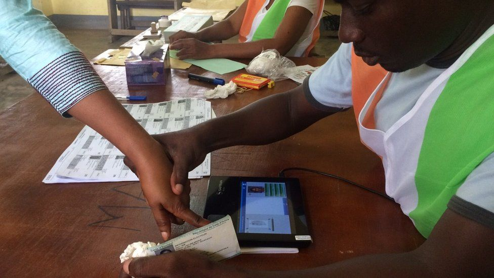 Election official helping a voter use the biometric system