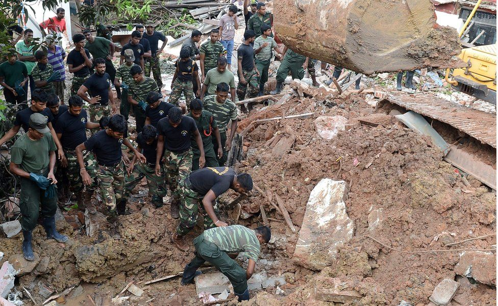 Sri Lankan military rescue workers recover the body of a man in the rescue operations at the site of a collapsed garbage dump in Colombo on April 15, 2017.