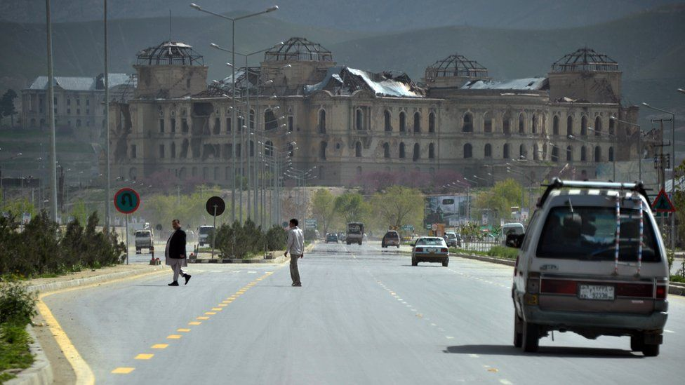 A general view shows Afghan people commuting on a road in front of the damaged remains of the Darul Aman palace in Kabul on April 28, 2012