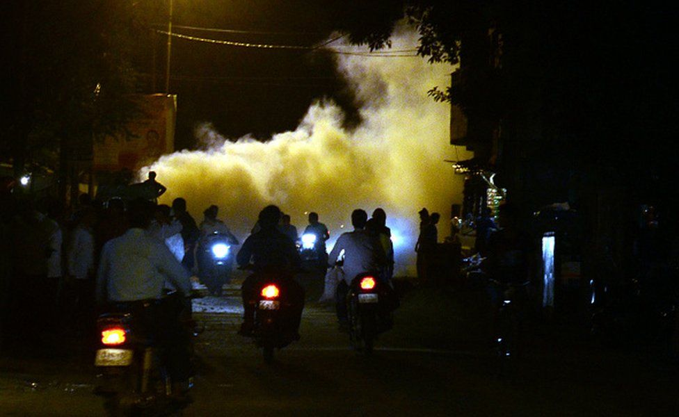 Indian people pass through smoke from fumigation in a busy old street of Allahabad on September 27,2016.